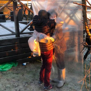 Two persons outdoors hugging through a plastic sheet. Photo.